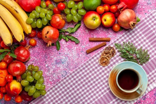 Vista superior da composição de frutas frescas frutas coloridas com xícara de chá e canela na superfície rosa