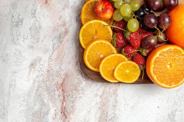 Vista superior da composição de frutas frescas, laranjas, uvas e morangos em uma superfície branca clara