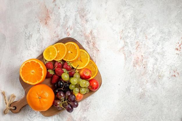 Vista superior da composição de frutas frescas, uvas, laranjas e morangos na superfície branca