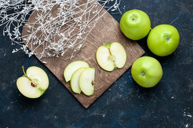 Vista superior da composição de maçãs verdes frescas com metade do corte fatiado alinhado na mesa escura, frutas frescas maduras