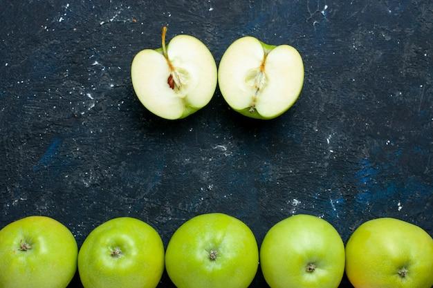 Vista superior da composição de maçãs verdes frescas com uma fatiada alinhada no escuro, frutas frescas maduras maduras