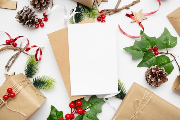 Vista superior da composição de natal com caixa de presente, fita, galhos de pinheiro, cones e anis na mesa branca