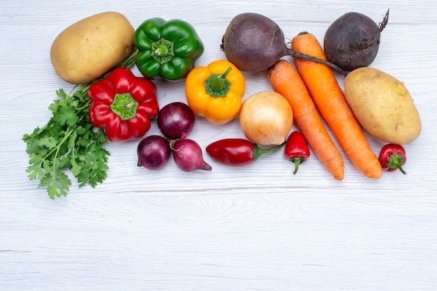 Vista superior da composição de vegetais com vegetais frescos, verdes, cenouras, cebolas e batatas, na mesa branca