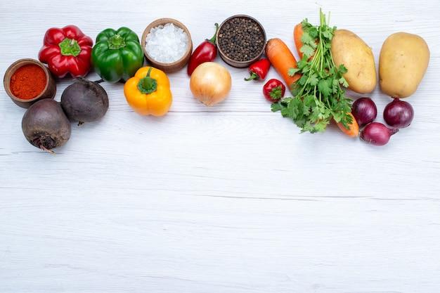 Vista superior da composição de vegetais com vegetais frescos, verdes, feijões crus, cenouras e batatas, à luz de fundo, refeição alimentar