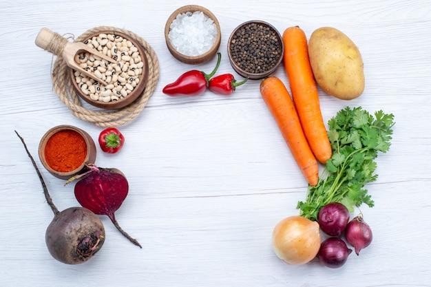 Vista superior da composição de vegetais com vegetais frescos, verdes, feijões crus, cenouras e batatas na mesa de luz, refeição alimentar, salada de vegetais