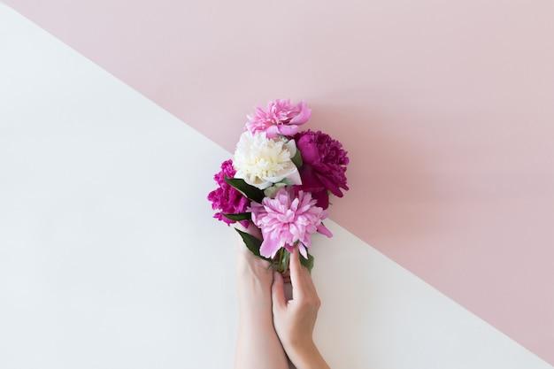 Vista superior da composição floral da linda flor rosa rosa na mão da mulher