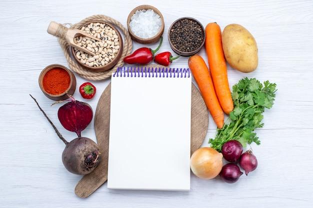 Vista superior da composição vegetal com legumes frescos, feijão cru, cenouras, bloco de notas e batatas na mesa branca