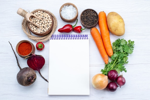 Vista superior da composição vegetal com legumes frescos, feijão crus, cenouras, verdes, bloco de notas e batatas, na mesa branca, comida, refeição, vegetal, salada