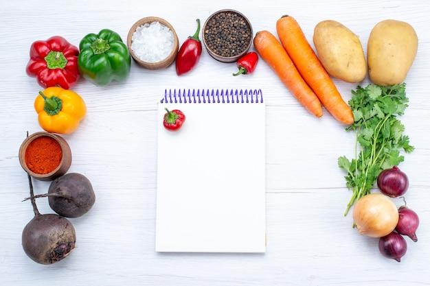 Vista superior da composição vegetal com legumes frescos verdes feijão cru, cenouras bloco de notas e batatas na mesa branca comida refeição salada de vegetais