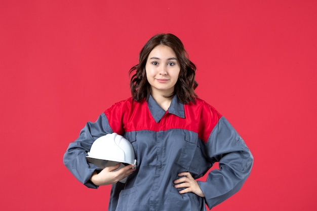 Vista superior da confiante construtora de uniforme e segurando um capacete sobre fundo vermelho isolado