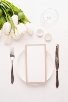 Vista superior da configuração da mesa com cartão de menu, talheres, tulipas brancas frescas, taça de vinho e velas para um jantar romântico na toalha de mesa de tecido branco