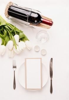 Vista superior da configuração da mesa com cartão de menu, talheres, tulipas brancas frescas, vinho e velas para um jantar romântico em toalha de mesa de tecido branco