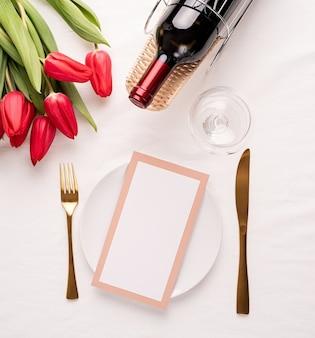 Vista superior da configuração da mesa com cartão de menu, talheres, tulipas vermelhas frescas e vinho na toalha de tecido branco