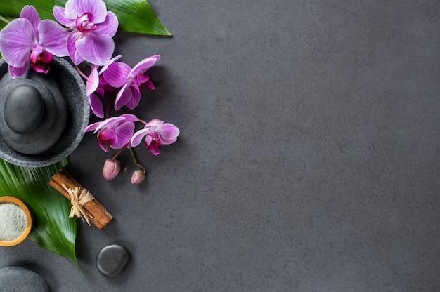 Vista superior da configuração de pedras quentes para massagem no quadro-negro com espaço de cópia.