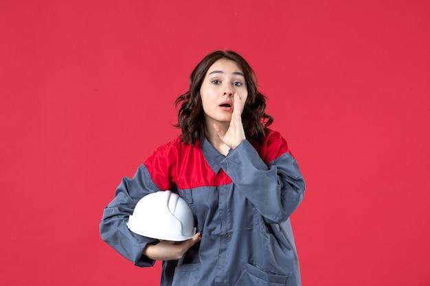 Vista superior da construtora de uniforme e segurando um capacete, chamando alguém sobre fundo vermelho isolado