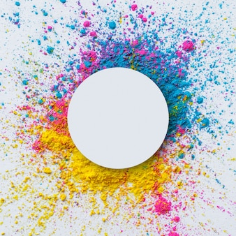 Vista superior da cor holi sobre um fundo branco com um círculo em branco