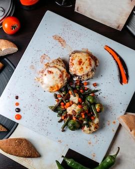 Vista superior da costeleta de carne frita com tomate e chese, guarnecida com couve-flor cozida, cenoura repolho pequeno e aspargos na superfície branca