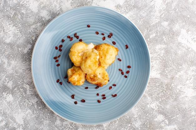 Vista superior da couve-flor cozida dentro de um prato azul na superfície branca