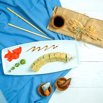 Vista superior da culinária japonesa tradicional sushi rollwith arroz camarão abacate e creme de queijo servido com molho de soja, gengibre e wasabi em azul e branco