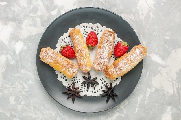 Vista superior da deliciosa massa de pão com açúcar em pó com morangos na superfície branca