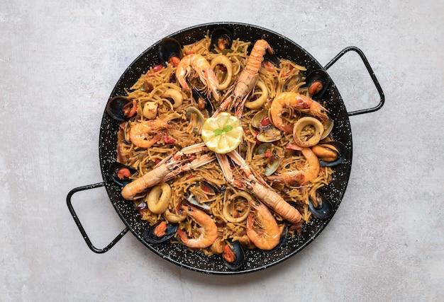 Vista superior da deliciosa paella com frutos do mar e anéis de cebola