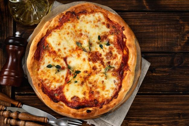 Vista superior da deliciosa pizza caseira margherita no fundo escuro de madeira