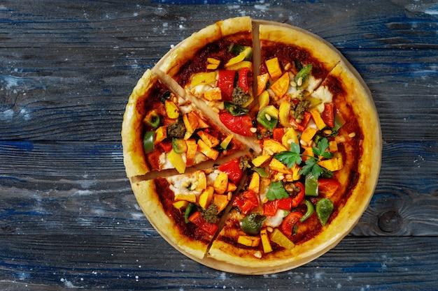 Vista superior da deliciosa pizza vegana cortada em pedaços sobre fundo azul