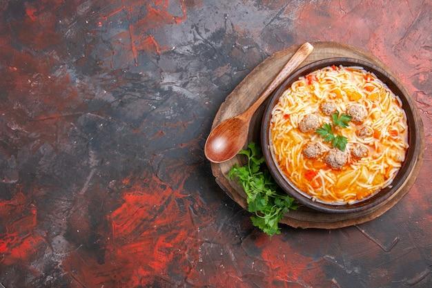 Vista superior da deliciosa sopa de macarrão com frango na tábua de madeira colher de verduras em fundo escuro
