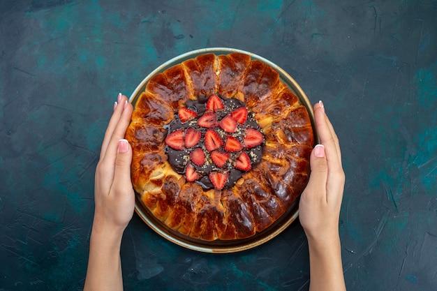 Vista superior da deliciosa torta de morango na superfície azul escura