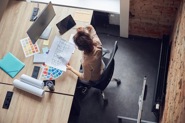 Vista superior da designer profissional feminina usando fones de ouvido, segurando uma planta enquanto trabalha