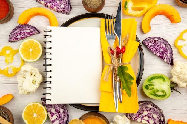 Vista superior da dieta escrita no bloco de notas amarrada com garfo e faca no guardanapo amarelo no prato redondo, corte os vegetais, especiarias diferentes em tigelas na mesa branca