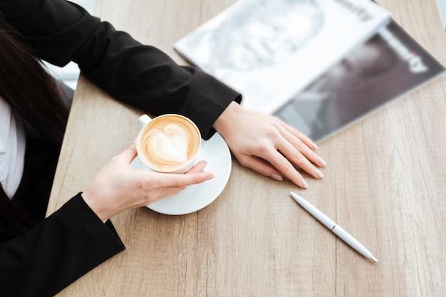 Vista superior da empresária sentado à mesa e tomando café