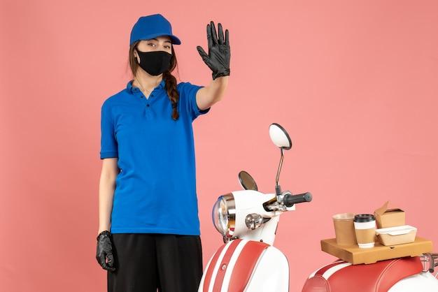 Vista superior da entregadora confiante usando luvas de máscara médica em pé ao lado da motocicleta com bolo de café mostrando cinco em um fundo de cor pastel de pêssego