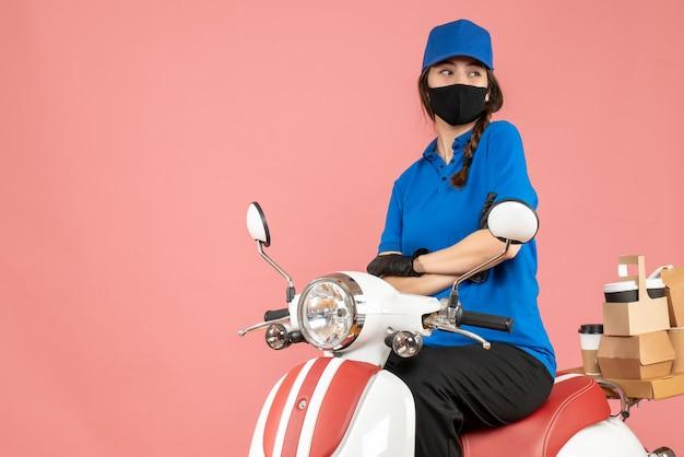 Vista superior da entregadora confiante usando máscara médica e luvas, sentada na scooter, entregando pedidos em fundo de pêssego pastel
