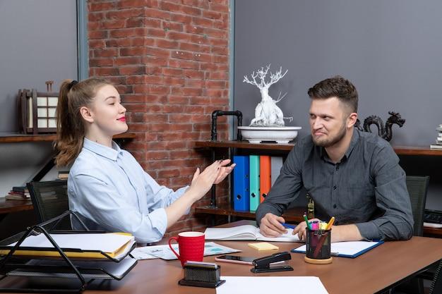 Vista superior da equipe administrativa sorridente e satisfeita, sentada à mesa, discutindo um tópico na sala de reuniões do escritório