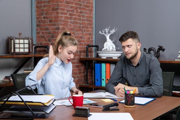 Vista superior da equipe de gestão concentrada e ocupada sentada à mesa, discutindo um tópico no escritório