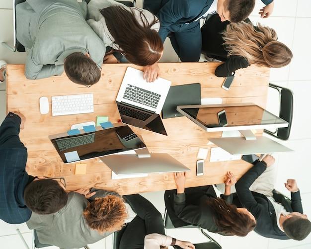 Vista superior da equipe de negócios sentada na mesa e olhando para a tela em branco