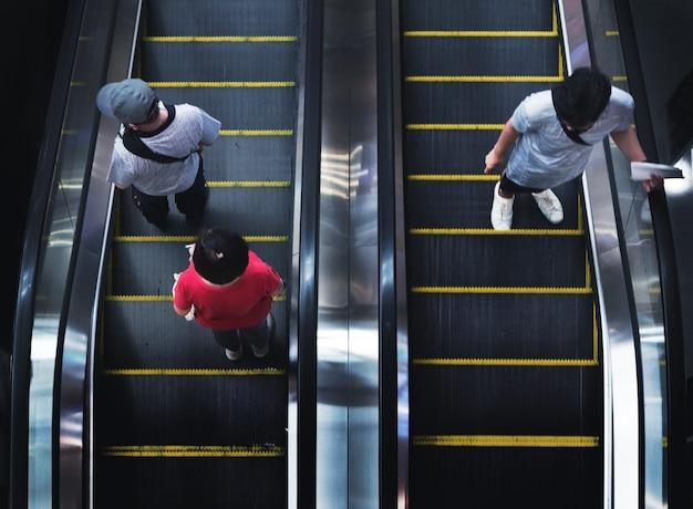 Vista superior da escada rolante de loja em shopping com cliente após fechamento aberto em pandemia de coronavírus