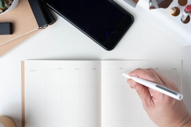 Vista superior da escrita de mão no planejador de calendário aberto para resolução de negócios