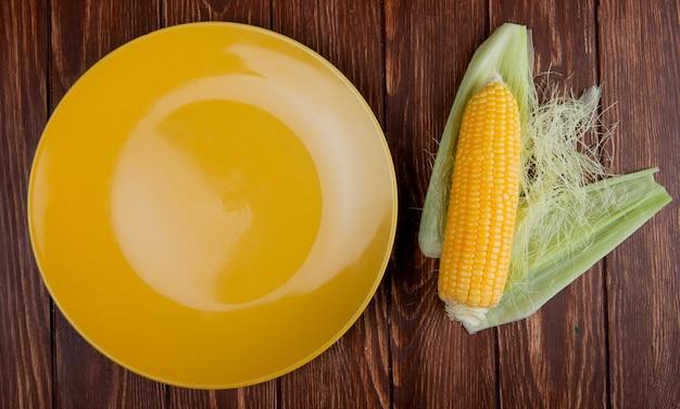 Vista superior da espiga de milho com casca e prato amarelo vazio na madeira