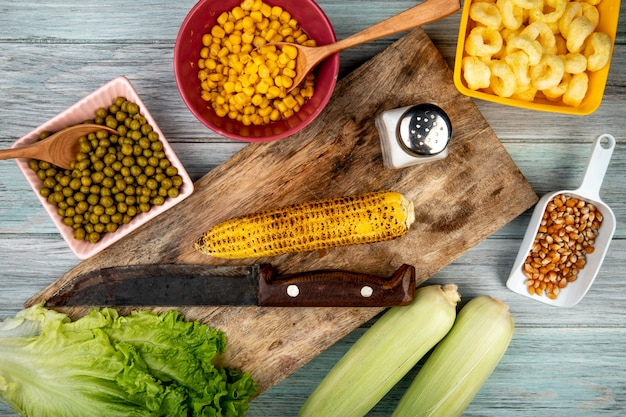 Vista superior da espiga de milho e faca na placa de corte com sal de alface de sementes de milho de ervilhas verdes na superfície de madeira