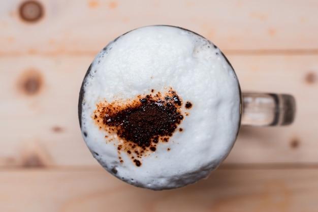Vista superior da espuma de café gelada em xícara e pó de café com grãos de café no piso de madeira.