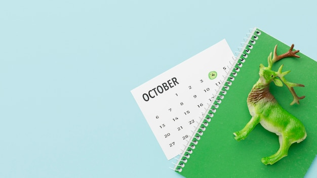 Vista superior da estatueta de veado com calendário e caderno para o dia do animal Foto gratuita