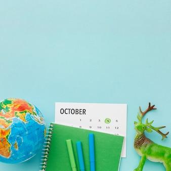 Vista superior da estatueta de veado com calendário e planeta terra para o dia animal