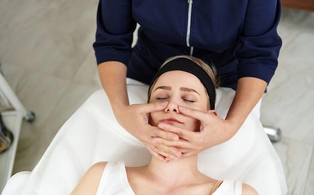 Vista superior da esteticista fazendo massagem anti-envelhecimento facial no rosto da mulher na clínica de spa. massagem profissional de drenagem linfática em moderno centro de spa