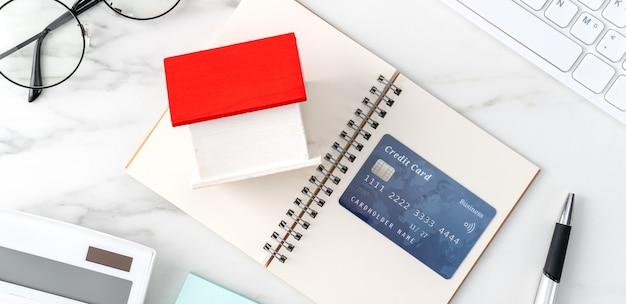 Vista superior da estimativa e do pagamento do imposto residencial com calculadora e cartão de crédito da internet.