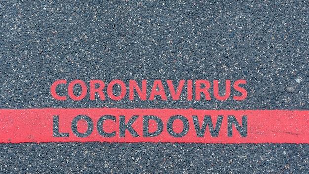Vista superior da estrada de asfalto com linha vermelha e texto coronavirus lockdown, restrição ou conceito de aviso de segurança
