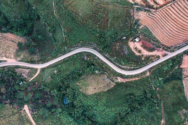 Vista superior da estrada de asfalto curva em uma colina na floresta na zona rural