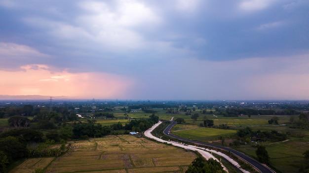 Vista superior da estrada rural passando pela floresta verde e pela montanha