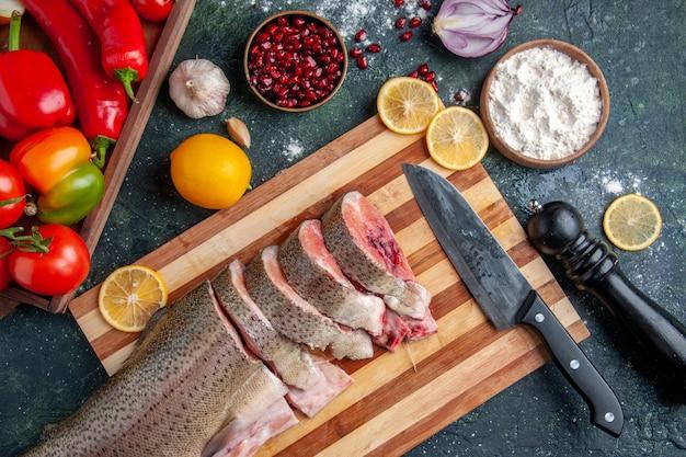 Vista superior da faca de fatias de peixe cru na tábua de cortar legumes na tábua de servir de madeira na mesa da cozinha